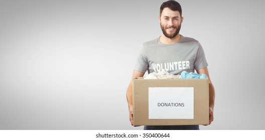 Portrait of man holding clothes donation box in office against grey vignette