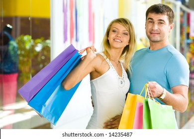 Portrait of man holding color shopping bags and embracing attractive girl