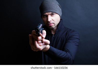 Portrait of a man holding gun against a black background