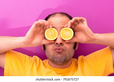 Portrait of a man holding two sliced lemons in his eyes and making silly faces