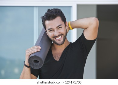Portrait of a man holding yoga mat and smiling with his hand behind his head