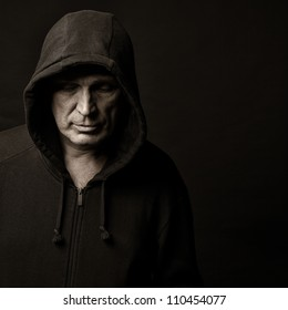 Portrait of the man in a hood against a dark background