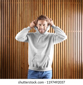 Portrait of man in hoodie sweater on wooden background. Space for design