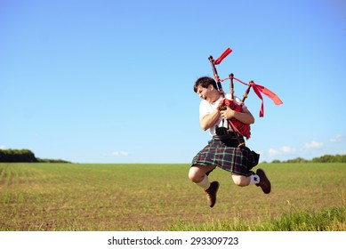 Portrait of man jumping high with pipes in Scottish traditional kilt on green outdoors copy space summer field