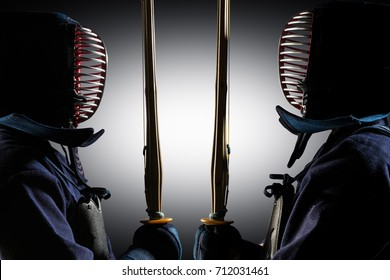 Portrait of man kendo fighter with shinai (bamboo sword). Shot in studio. Isolated with clipping path on grey background