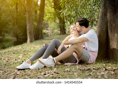 Portrait of a man kiss girlfriend under tree in park, happy young couple enjoying a day in the park together
