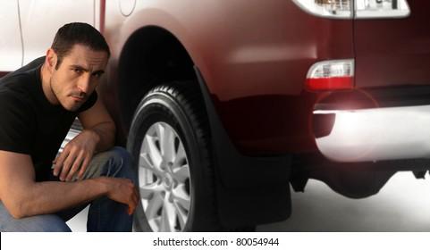 Portrait of a man kneeling down by large pickup truck
