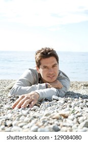 Portrait of a man laying down on the shore of a white pebble beach smiling with a blue sky and the sea in the background.