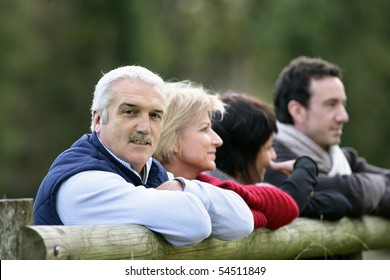 Portrait of a man leaning against a wooden fence