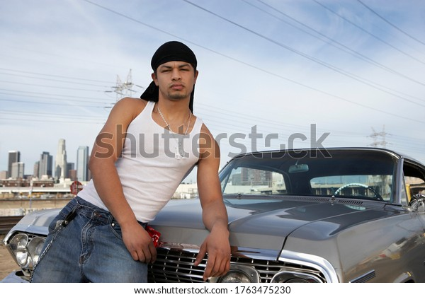 Portrait of man leaning on car