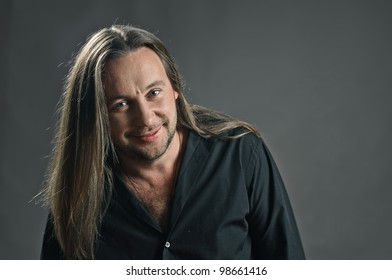 portrait of man with long hair on grey