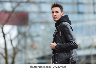Portrait of man look around. Stylish clothing wear. Autumn and winter weather. Jacket with white sneakers. Blur background, proffesional photo.