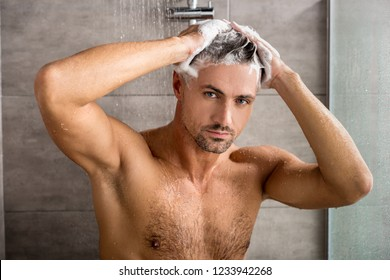 portrait of man looking at camera while washing hair with shampoo and taking shower