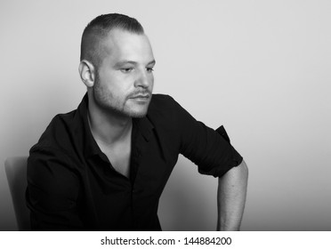 portrait of a man looking down, black and white photo, sitting with a black shirt and three-day stubble