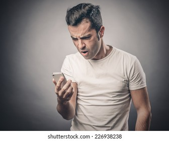 Portrait of man looking at his smartphone in confusion