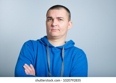 portrait of a man looking skeptical, wearing a blue hoodie, isolated on a gray background