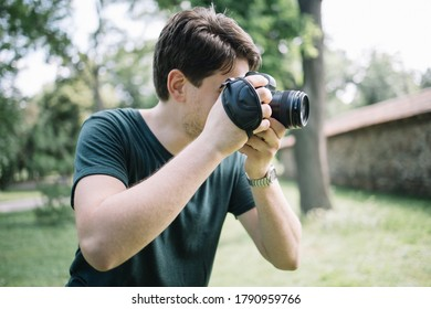 Portrait of man looking through camera viewfinder. Close-up view of photographer looking through camera viewfinder in park.