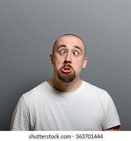 Portrait of a man making funny face against gray background