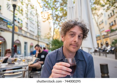 Portrait of a man making a toast as he sits outside at a cafe in Barcelona. Concept of having fun enjoying vacation in Europe.