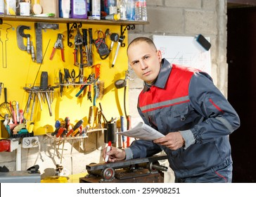 Portrait of a man mechanic with drawings and pencil in hand