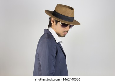 Portrait Man in Navy Blue Suit and White Shirt and Hat and Glasses on Right Pose. Man in Navy Blue suit with brown straw hat and black glasses or eyewear on grey background in smart style