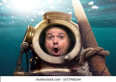 The Portrait of man in old diving suit and helmet under water. Funny shocked diver in retro equipment look to camera.