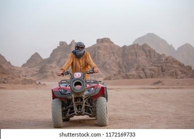 Portrait of a man on an ATV. Quad bikes safari in desert near Sharm El Sheikh, Egypt. Powerful fast off-road four-wheel drive motorcycles in sandy desert, rally against high mountains