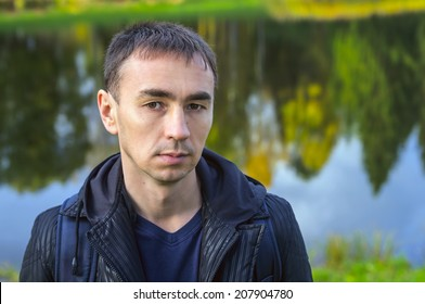 Portrait of a man on the background of the autumn pond.