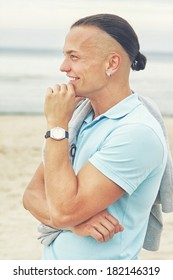 Portrait of man on the beach posing in blue t-shirt