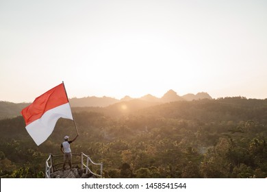 portrait of man on top of the hill in the morning rising indonesian flag celebrating independence day