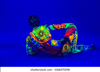 Portrait of man painted in fluorescent powder. Portrait of man with Fluorescent Creative MakeUp, Art Design of  colorful  Make-Up