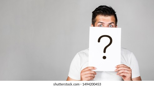 Portrait of man, peeking behind of interrogation symbol. Question mark, symbol. Pensive male. Man a question. Doubtful man holding Question Mark. Problems and solutions. Copy space.