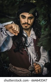 Portrait of man in a pirate costume poses outdoor.