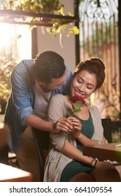 Portrait of man presenting red rose to smiling Asian woman, meeting for date in cafe