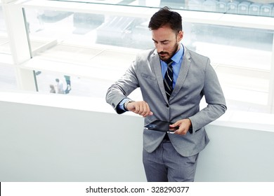 Portrait of a man professional banker watching on his wristwatch while standing with touch pad in modern interior, young skilled managing director using digital tablet while waiting for partners