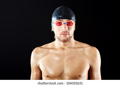 Portrait of a man professional  swimmer posing at studio over black background.