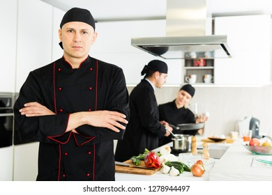 Portrait of the man proffesional who is posing in the kitchen at the cafe.