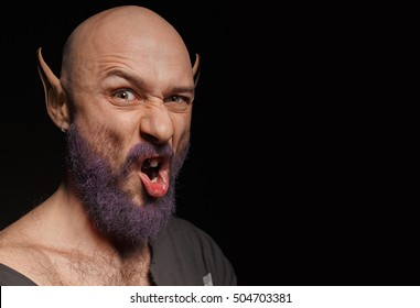 Portrait of a man with a purple beard, long ears and a silver tooth. Holiday makeup on Halloween. Space for text.