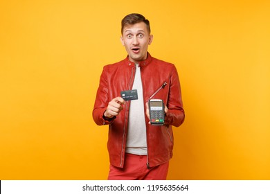 Portrait man in red leather jacket, t-shirt hold wireless bank payment terminal to process acquire credit card payments isolated on yellow background. People lifestyle concept. Advertising area