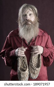 portrait of a man in a red shirt with long hair beard and mustache with a baton and bast shoes in hands studio on a burgundy background