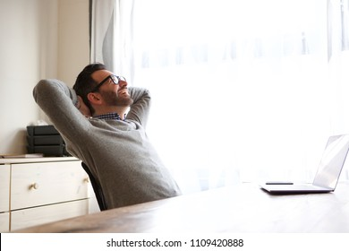Portrait of man relaxing with hands behind head in front of laptop