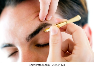Portrait of man removing eyebrow hairs with tweezing.