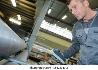 portrait of a man repairing a rolling machine