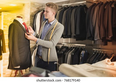 Portrait of man seller measuring business style jacket in the shop