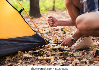 Portrait of a man setting up a tent on a camping trip