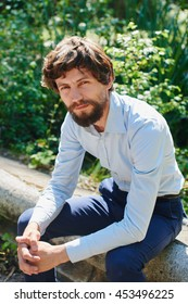 Portrait of a man in shirt and trousers sitting in a Park