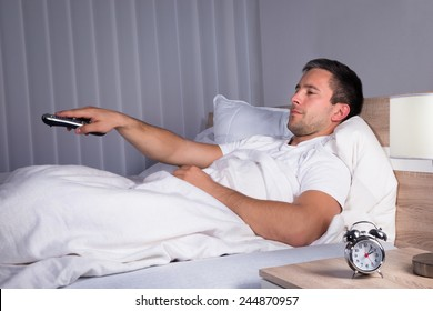Portrait Of A Man Sitting On Bed Changing Television Channels With Remote