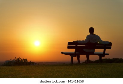 Portrait of a man sitting on a bench enjoying the Sunset