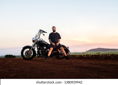 Portrait of a man sitting on his black custom classic motorcycle