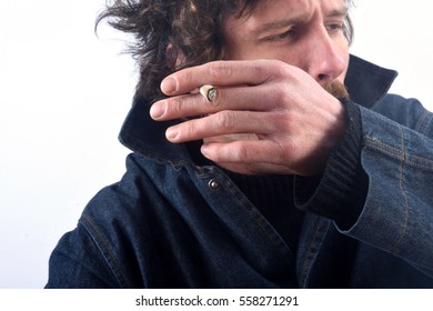 Portrait of a man smoking tobacco and coughing on white background